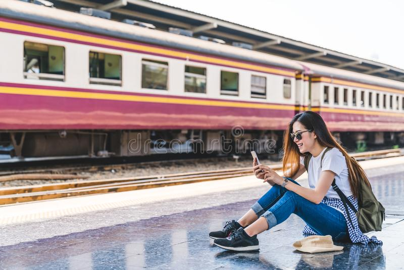 Asian tourist teenage girl at train station using smartphone map, social media check-in, or buy ticket booking stock photos