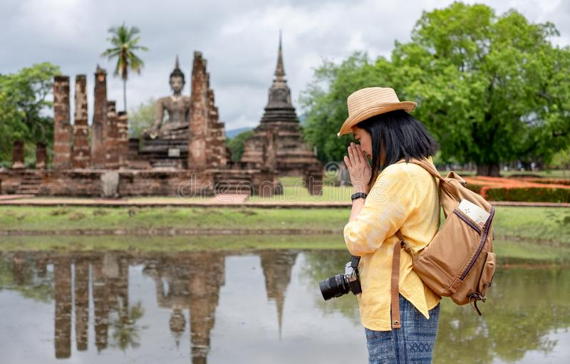 Asian tourist woman pay respect to buddha at ancient of pagoda temple thai architecture at Sukhothai,Thailand. Female traveler in. Casual thai cloths style royalty free stock photo
