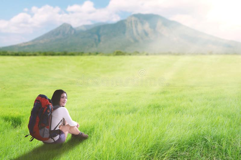 Asian tourist woman sitting on a greenery hill trail with backpack royalty free stock photography