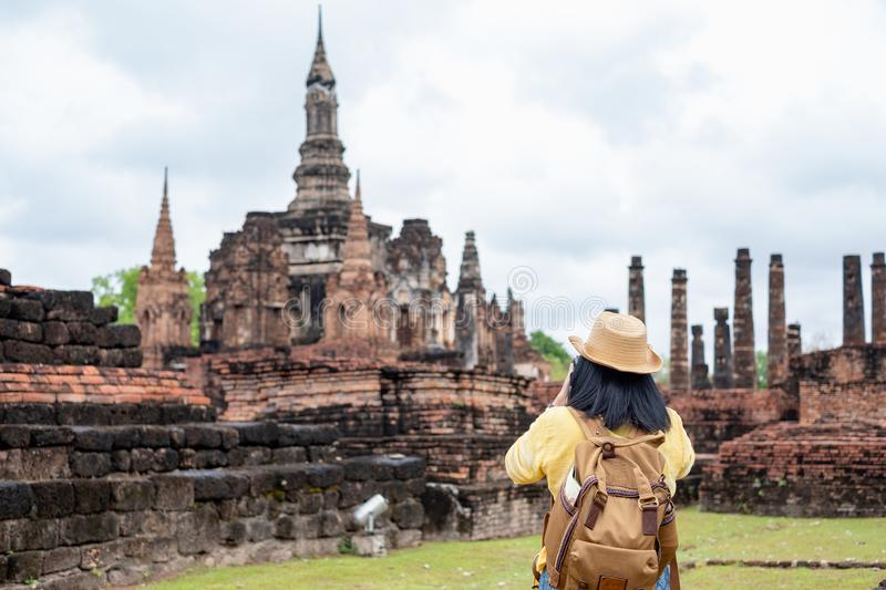 Asian tourist woman take a photo of ancient of pagoda temple thai architecture at Sukhothai Historical Park,Thailand. Female. Traveler in casual thai cloths stock image
