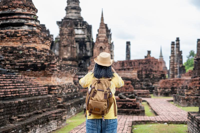 Asian tourist woman take a photo of ancient of pagoda temple thai architecture at Sukhothai Historical Park,Thailand. Female. Traveler in casual thai cloths royalty free stock image