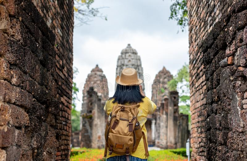 Asian tourist woman take a photo of ancient of pagoda temple thai architecture at Sukhothai,Thailand. Female traveler in casual t. Hai cloths style visiting city royalty free stock photos