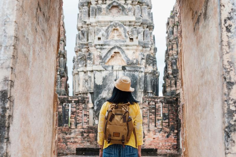 Asian tourist woman take a photo of ancient of pagoda temple thai architecture at Sukhothai,Thailand. Female traveler in casual t. Hai cloths style visiting city royalty free stock images