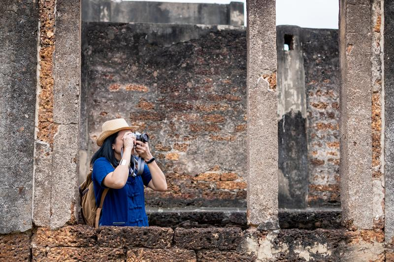 Asian tourist woman take a photo of ancient of temple thai architecture at Sukhothai,Thailand. Female traveler in casual thai. Cloths style visiting city stock images