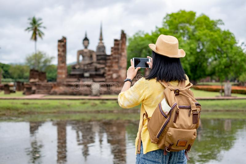 Asian tourist woman use mobile take a photo of ancient of pagoda. Temple thai architecture at Sukhothai Historical Park,Thailand. Female traveler in casual thai royalty free stock photos