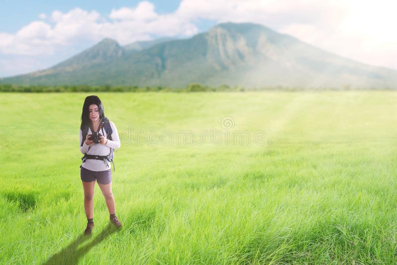 Asian tourist woman walking on a greenery hill trail with backpack and camera stock photography