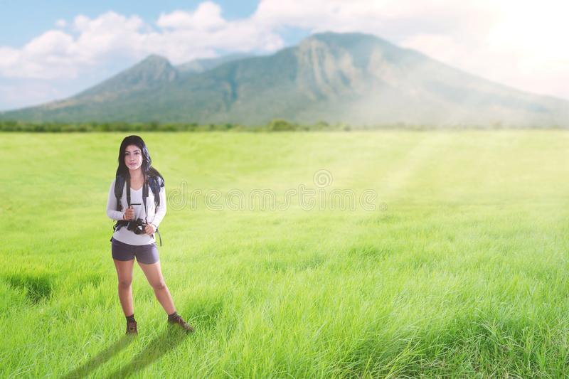 Asian tourist woman walking on a greenery hill trail with backpack and camera.  royalty free stock images