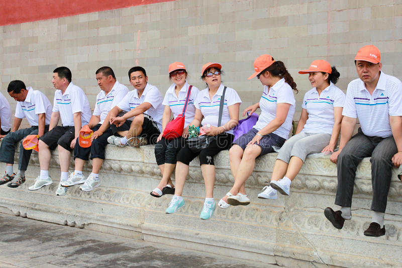 Asian tourists sitting and taking break on a low wall in Forbidden City, the Palace Museum, north of Tiananmen Square. Beijing, C royalty free stock photo