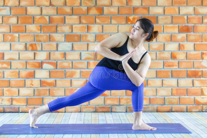 Asian trainee strong woman practicing difficult yoga pose in a concrete background.  royalty free stock photos