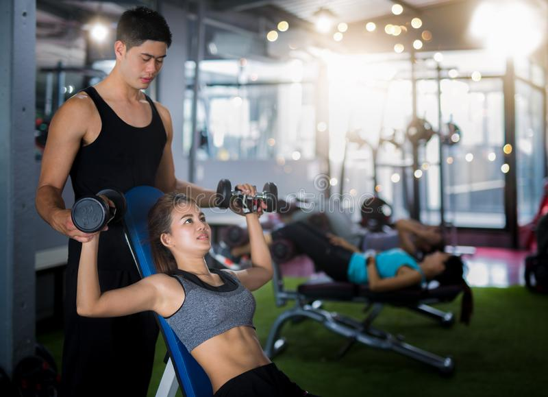 Asian trainer and lady take personal training in fitness club stock photo