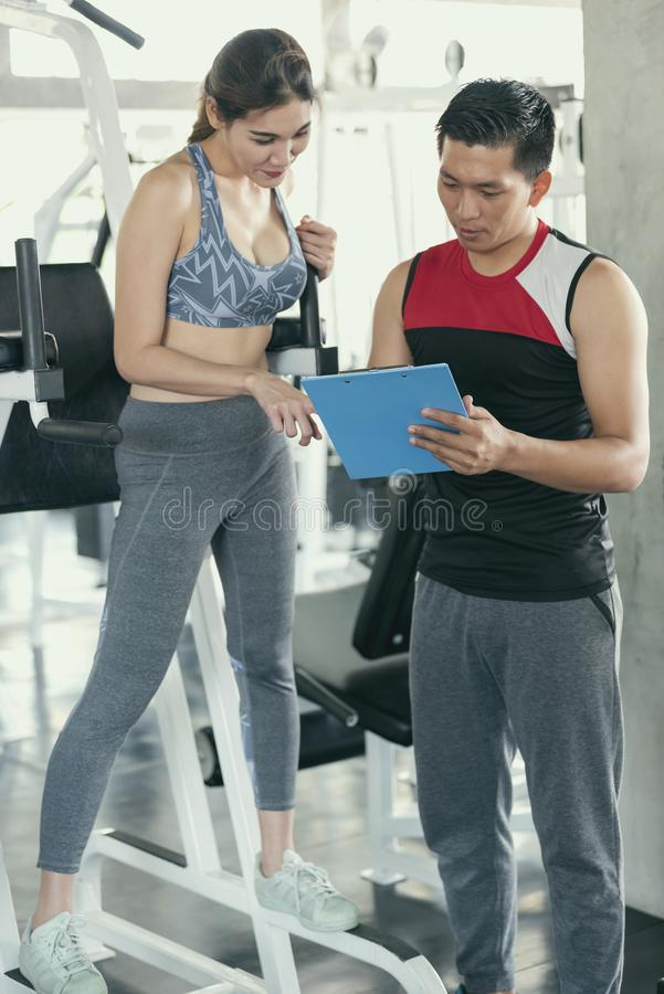Asian trainer with woman in fitness gym. Personal coach royalty free stock photography