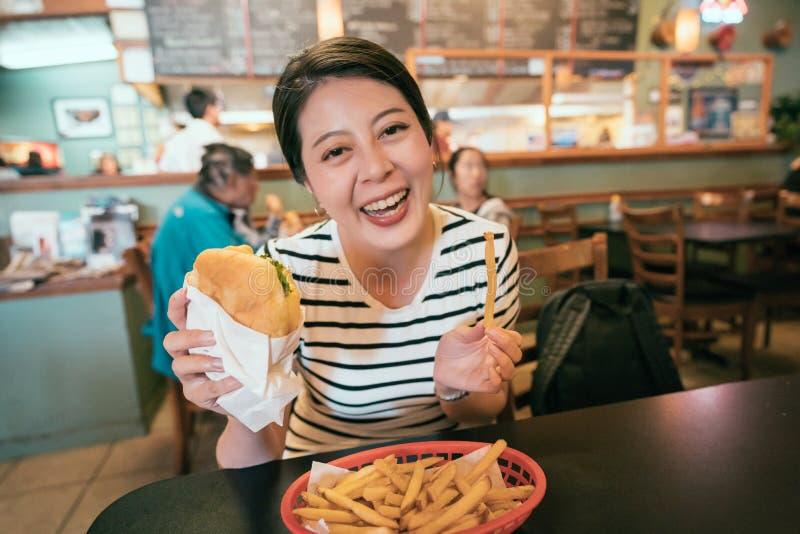 Asian traveler holding fries and hamburger stock photo