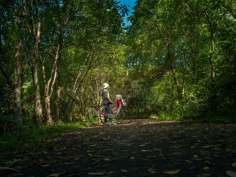 Asian traveler holiday relax with bicycle in nature park. Asian traveler holiday relax drinking water with bicycle in Bang Krachao nature park royalty free stock photography