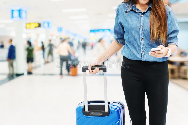 Asian Traveler women looking for flight in smartphone at airport terminal Travel concept. Asian Traveler woman looking for flight in smartphone at airport stock image