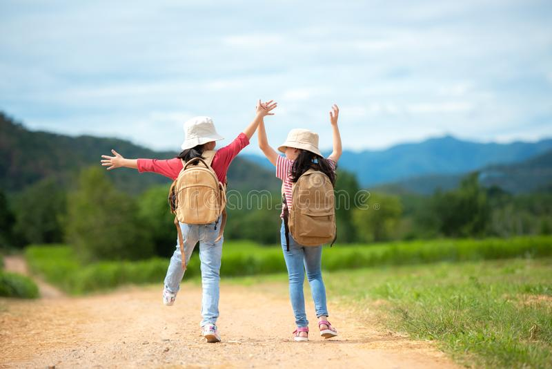 Asian two girl raise arms and jumping on the nature road, outdoors adventure and tourism for destination and leisure trips with mo royalty free stock photo