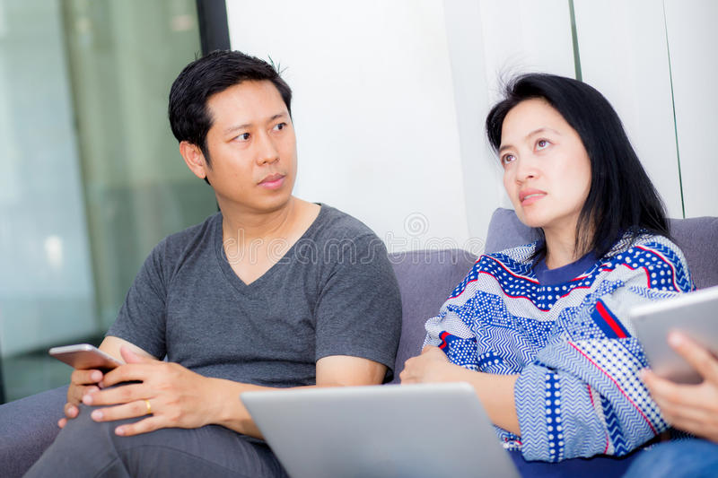 Asian two people friends online with multiple devices and talking on sofa. Asian two people friends online with multiple devices and talking sitting on a sofa royalty free stock image