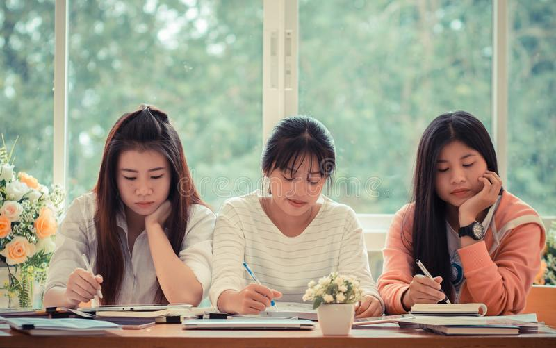 Asian University or college students studying together with tablet,laptop and documents paper for report near windows in stock image