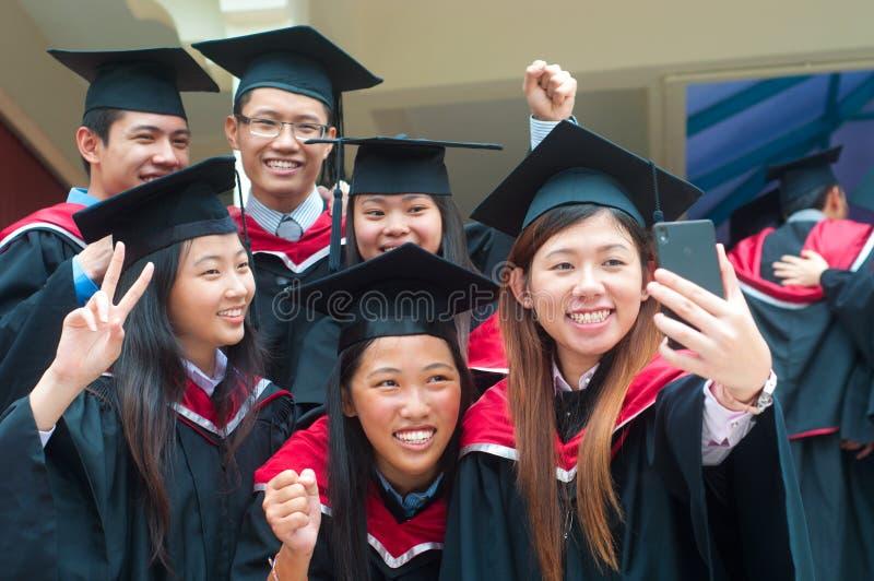Asian university graduates. Taking photo with handphone royalty free stock photo