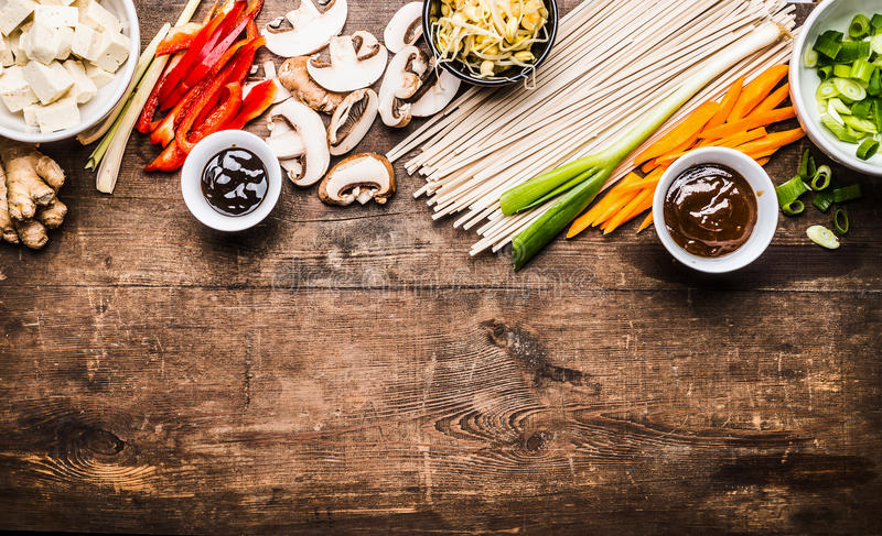 Asian vegetarian cooking ingredients for stir fry with tofu, noodles, ginger, cut vegetables, Sprout,green onion , lemongrass, hoi. Sin and austern sauce on stock photo