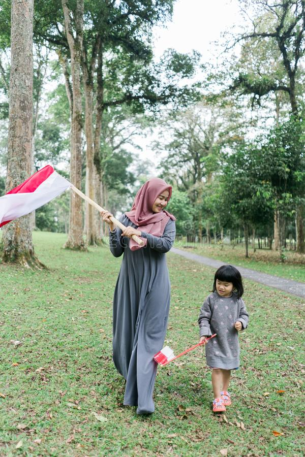 Asian veiled mother wit doughter flapping Indonesian flag. Asian veiled mother with daughter flapping Indonesian flag with spirit in the park royalty free stock images