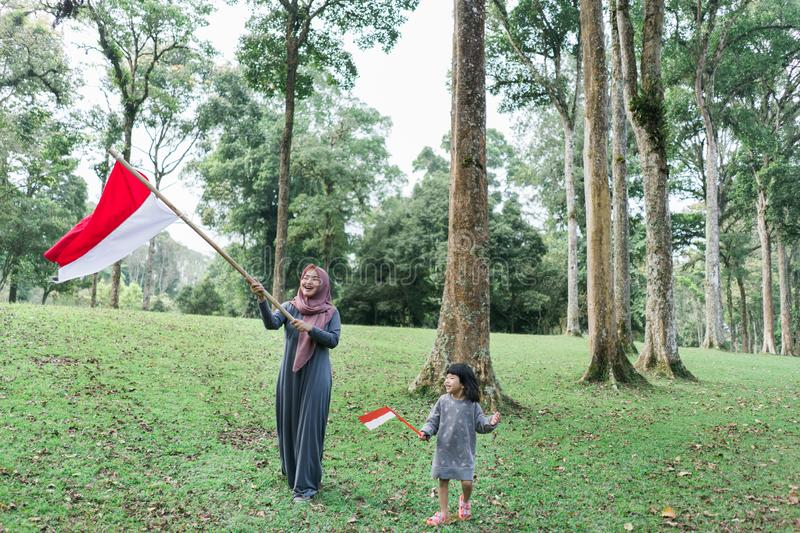 Asian veiled mother wit doughter flapping Indonesian flag. Asian veiled mother with daughter flapping Indonesian flag with spirit in the park stock photos