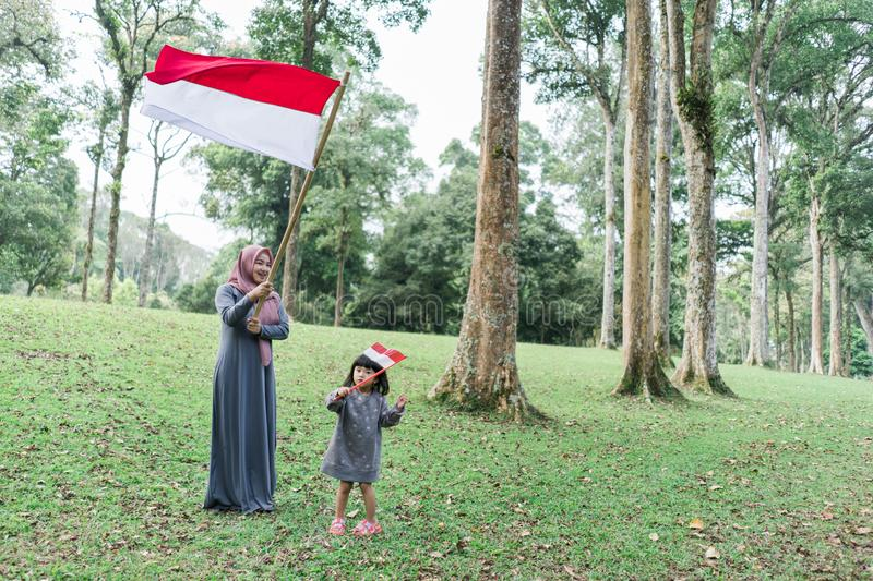Asian veiled mother wit doughter flapping Indonesian flag. Asian veiled mother with daughter flapping Indonesian flag with spirit in the park royalty free stock photo