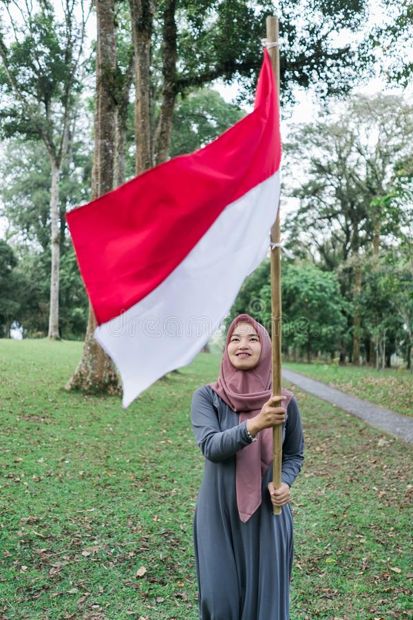 Asian veiled woman flapping Indonesian flag. Asian veiled women flapping Indonesian flag with spirit in the park stock photography