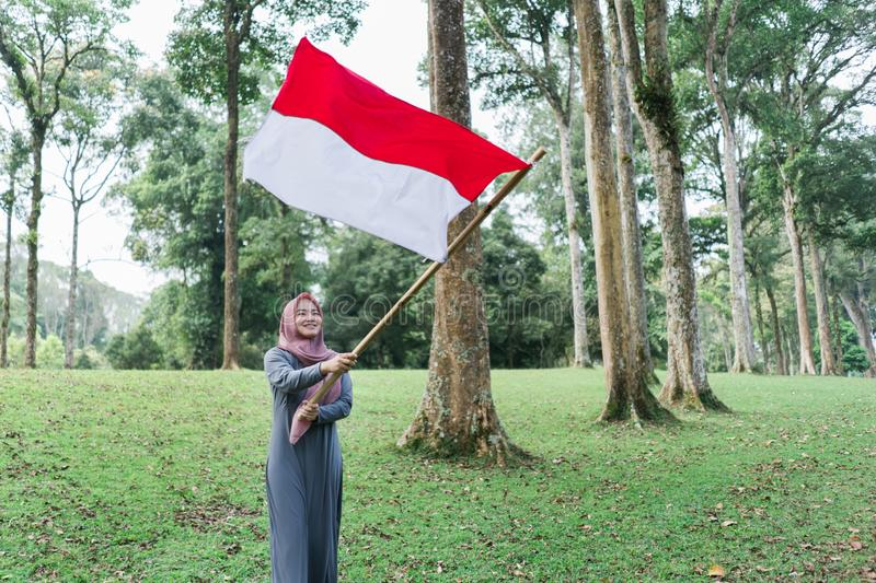Asian veiled woman flapping Indonesian flag. Asian veiled women flapping Indonesian flag with spirit in the park stock photos