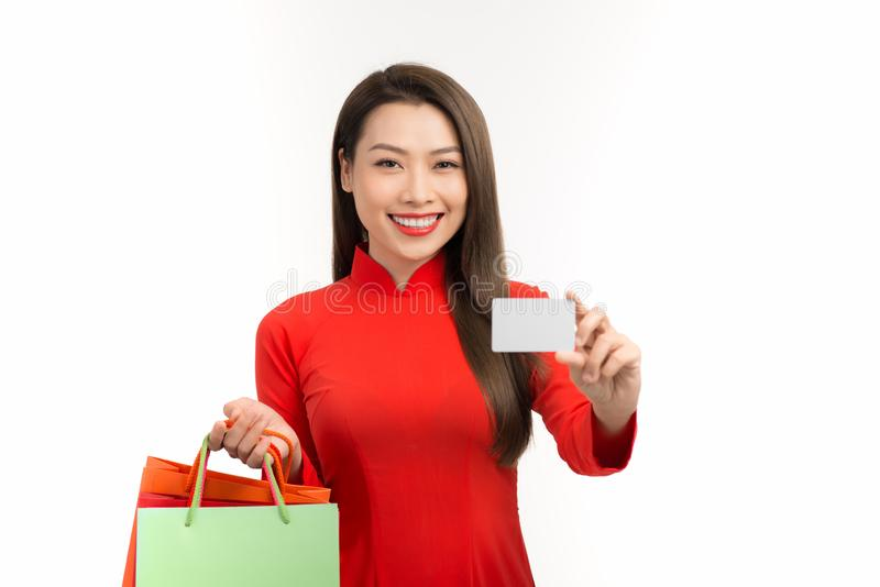 Asian Vietnamese woman in Ao dai traditional red dress holding blank Credit for Shopping in Lunar New Year Festival.  royalty free stock photos