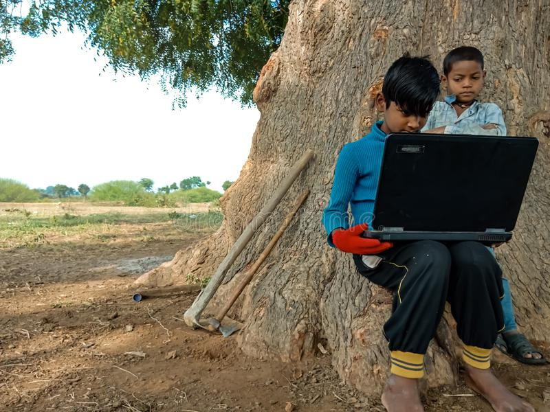 Asian village kids operating laptop at natural background in india January 2020 stock images