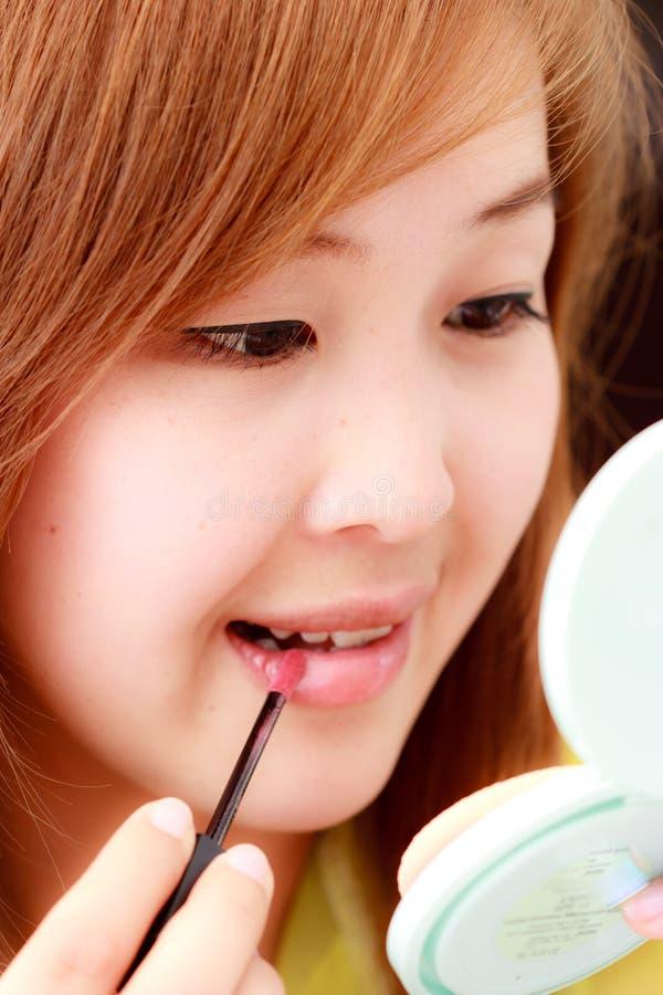 Asian waman making up her face. Asian young woman and cosmetics stock photos
