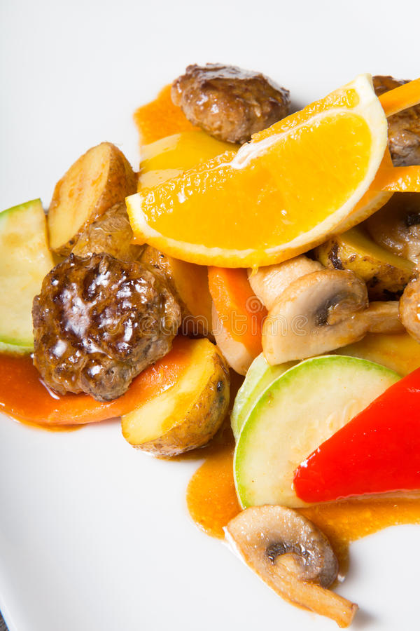 Asian warm salad with meatballs. And orange stock image