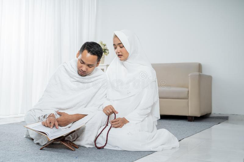 Asian wife and husband praying with Al-Qur`an and tasbih. In white traditional clothes royalty free stock photo