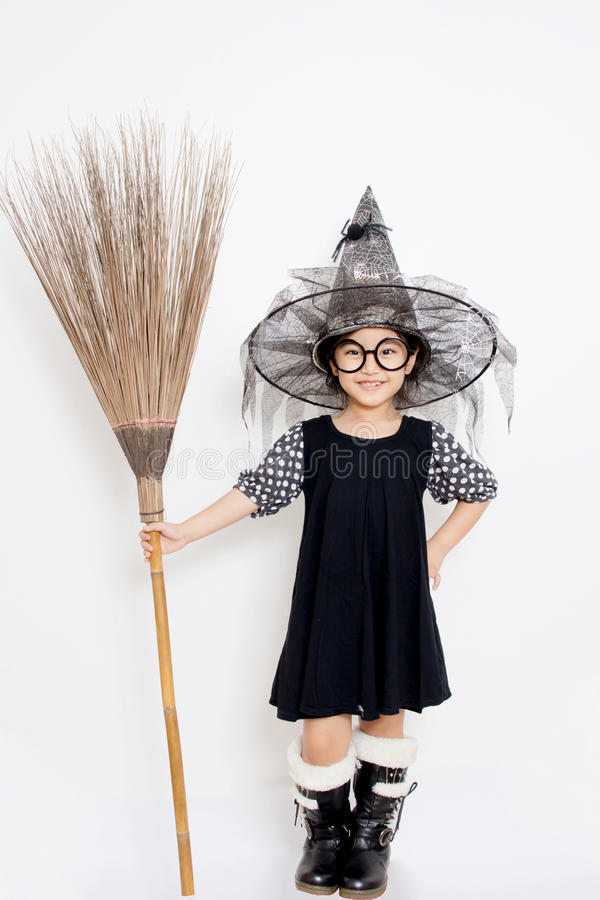 Asian witch child holding magic broom royalty free stock photos