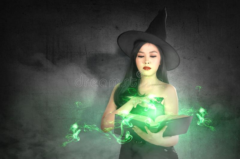 Asian witch woman in hat learns the spell from the magic book stock photography