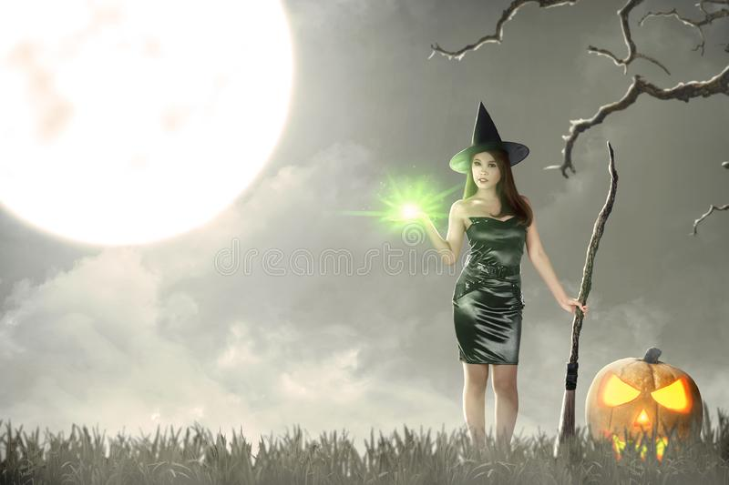 Asian witch woman with magic shine on her hand and broom royalty free stock images