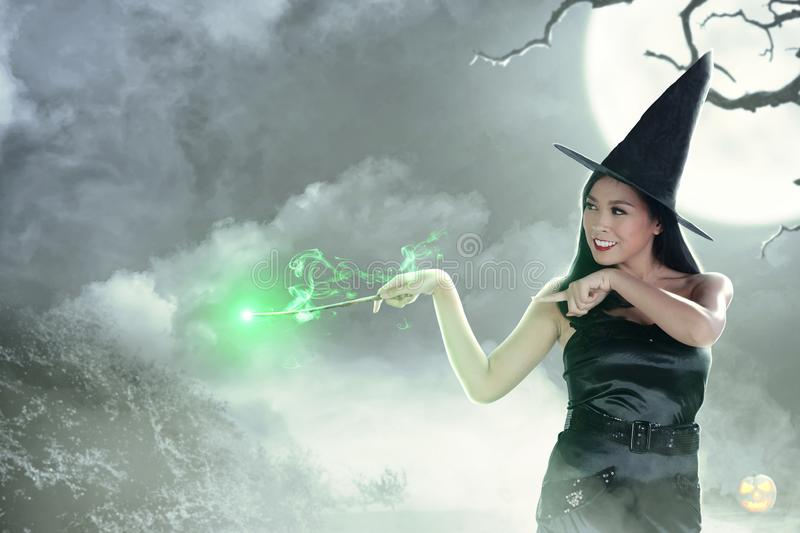 Asian witch woman using the wand with magic shine stock image