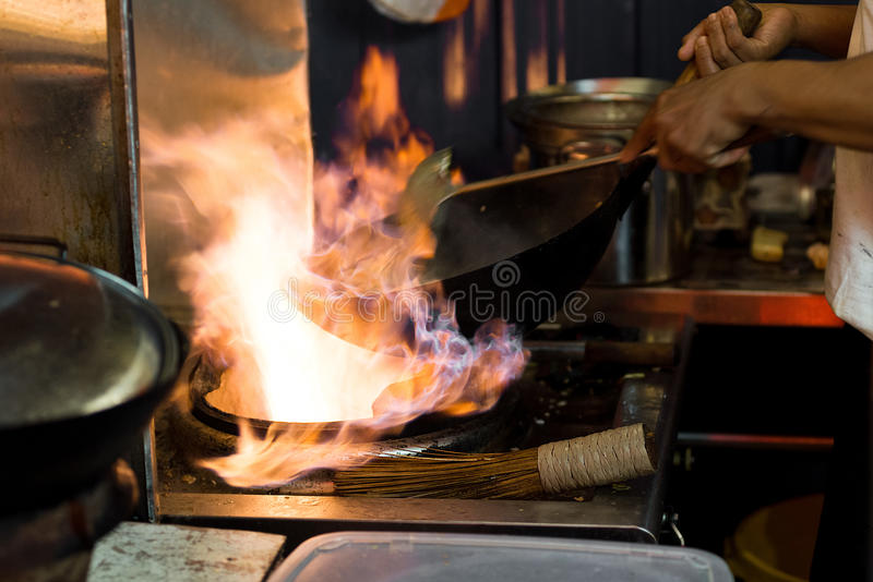Asian wok cooking with flames in an open style street food kitc. Hen stock photography