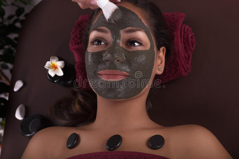 Asian womam in spa treatment,facial mask with algae. Cosmetologist doing massage on the woman`s face in spa salon royalty free stock images