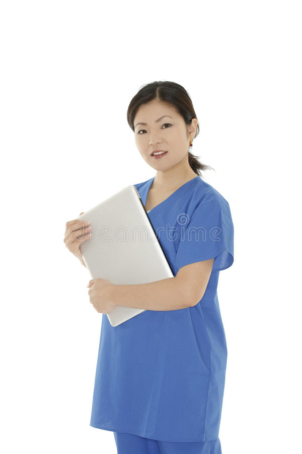 Asian woman doctor or nurse holding a laptop computer. Beautiful Asian woman doctor or nurse wearing scrubs and holding a laptop computer isolated on a white royalty free stock photos