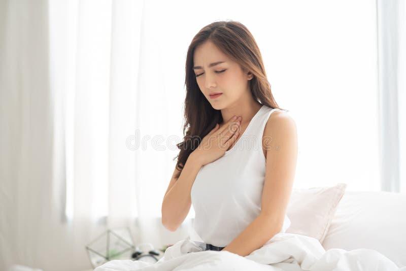 Asian Woman with Acid Reflux. Asian Beautiful Woman with Acid Reflux on her bed. Illness, Disease, Symptom royalty free stock photos
