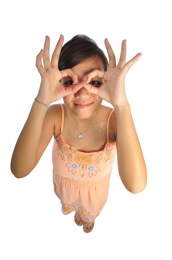 Asian Woman acting cute with hand gestures. Beautiful young Asian Woman picture taken from the top to give a big doll head effect royalty free stock images