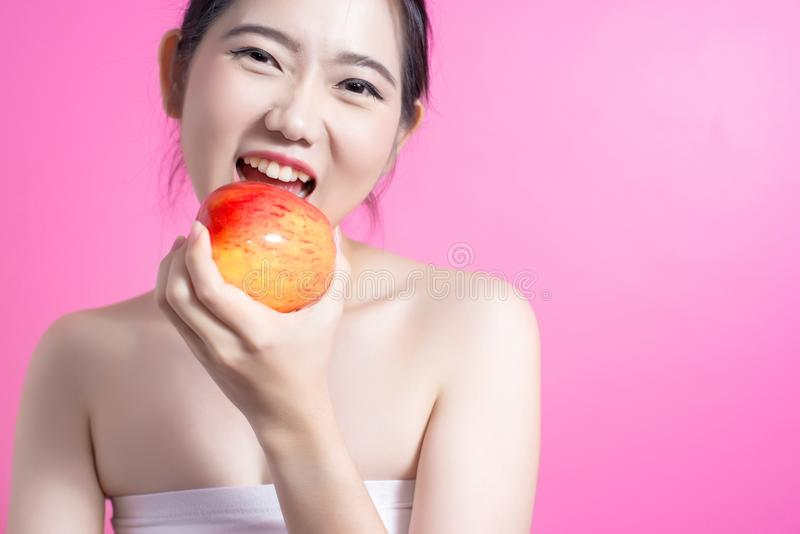 Asian woman with apple concept. She smiling and holding apple. Beauty face and natural makeup. Isolated over pink background. stock images