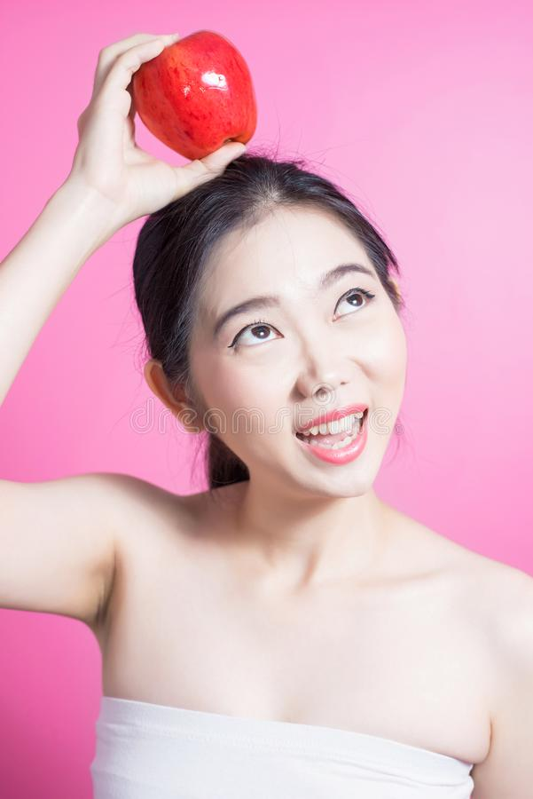 Asian woman with apple concept. She smiling and holding apple. Beauty face and natural makeup. Isolated over pink background. stock image