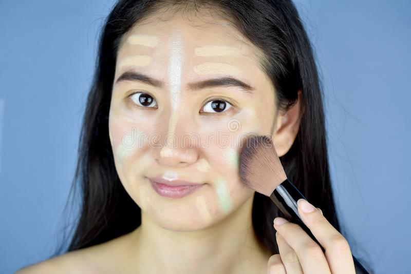 Asian woman applying cosmetics makeup and using color correction concealer, Face skin preparing before makeup. stock photography