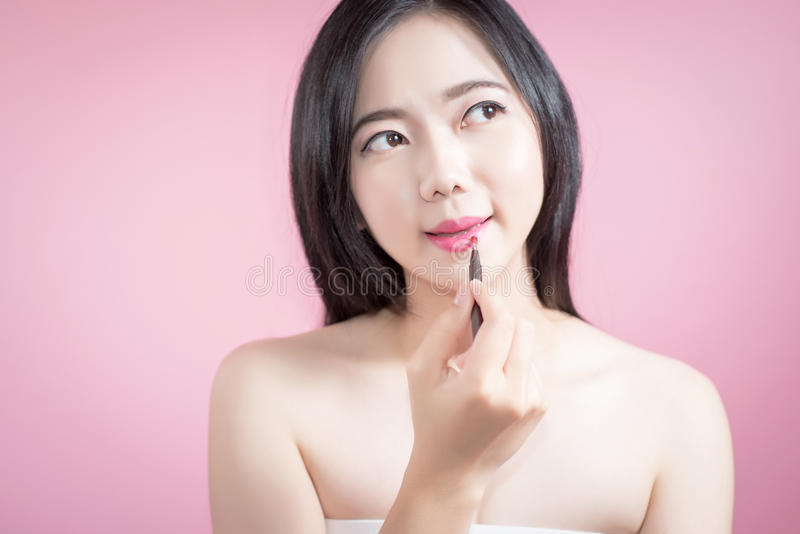 Asian woman applying pink lipstick on her lips, Beauty face and natural makeup, White background isolated. royalty free stock photography