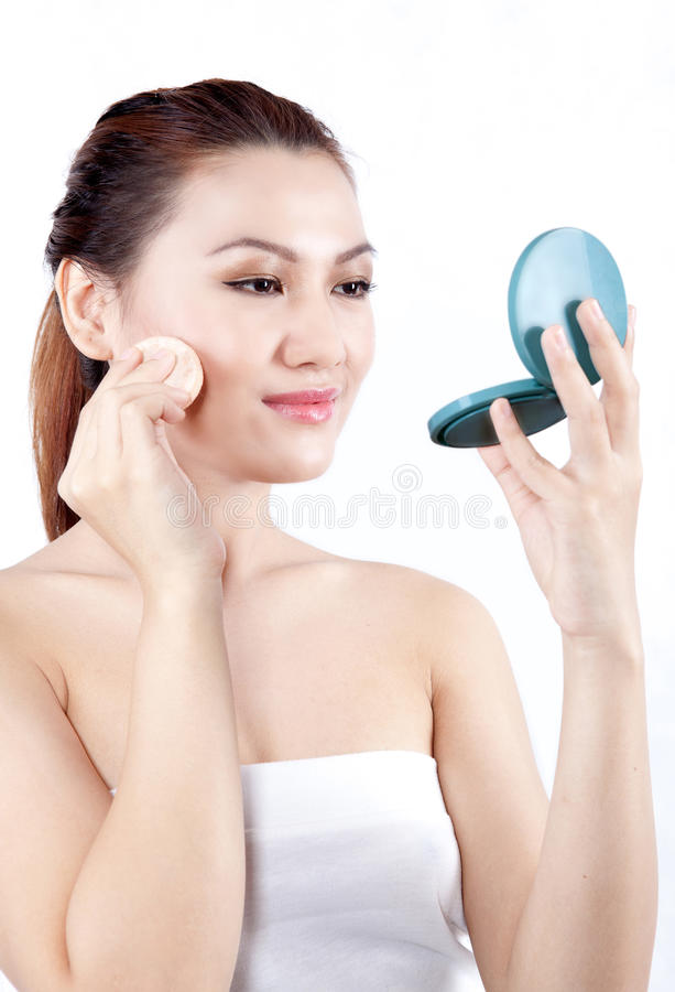Asian Woman Applying Powder On Her Face Royalty Free Stock Photography