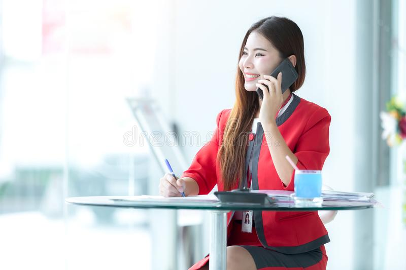 Asian woman auto business, car sale, gesture and people concept - smiling businessman talking on smartphone over auto show royalty free stock image