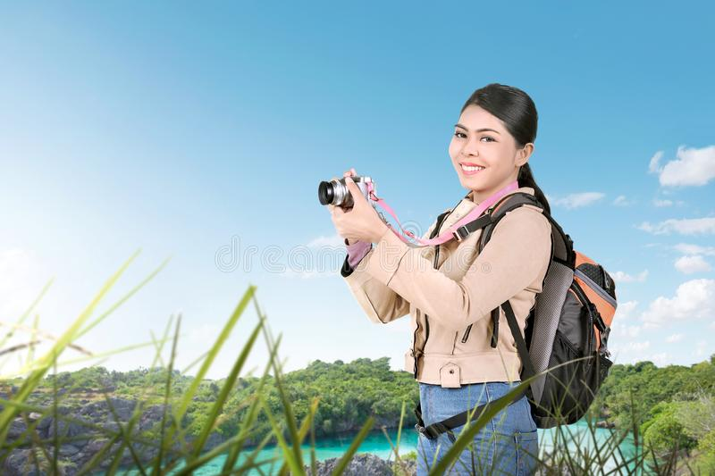 Asian woman with a backpack holding a camera to take pictures stock photo