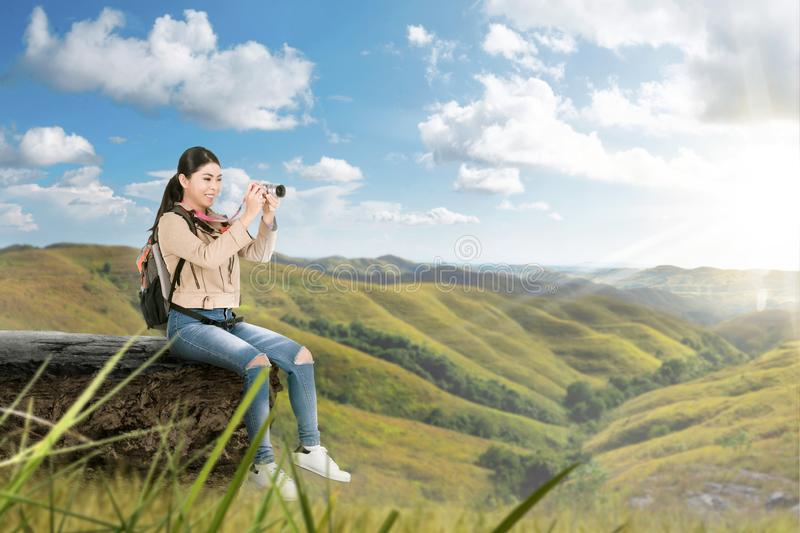 Asian woman with a backpack sitting on the edge stone and holding a camera to take pictures royalty free stock photos